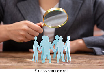 Businesswoman Looking Human Figures With Magnifying Glass