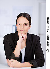 Businesswoman Looking In Camera While Leaning On Desk