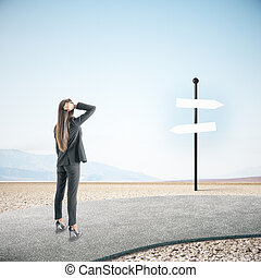 Businesswoman looking on empty sign post.