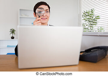 Businesswoman looking through  a magnifying glass