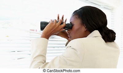 Businesswoman looking through blinds with binoculars in the office