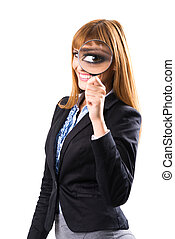 Businesswoman looking through magnifying glass