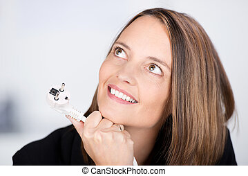 Businesswoman Looking Up While Holding Electric Plug