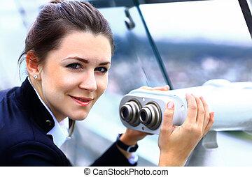 Businesswoman looks through telescope on the city building