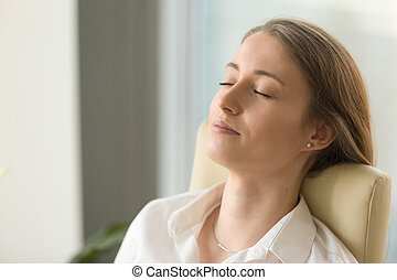 Businesswoman lying on back chair with closed eyes
