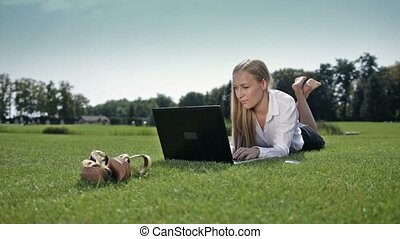 Businesswoman lying on green grass with laptop