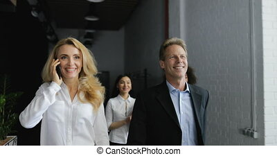Businesswoman Make Phone Call Walking With Happy Smiling Business People Team In Modern Creative Office
