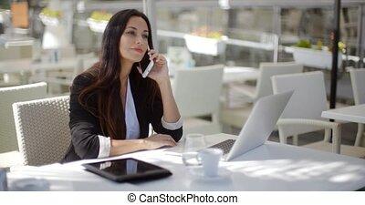 Businesswoman making a call at a restaurant