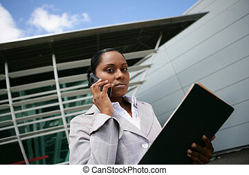 Businesswoman making a call outdoors