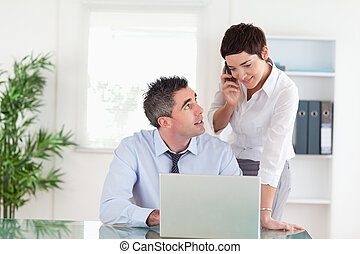 Businesswoman making a phone call while her colleague is working on a laptop in an office