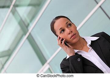 businesswoman making call near office