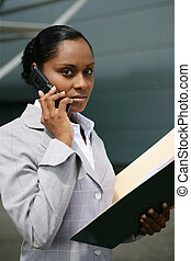 Businesswoman making call whilst reading document
