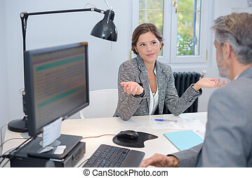 Businesswoman making questioning gesture to male colleague