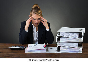 Businesswoman Massaging Head While Looking At Folders