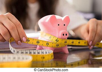 Businesswoman Measuring Piggybank With Measuring Tape