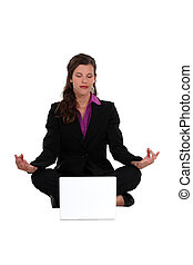 Businesswoman meditating in front of laptop
