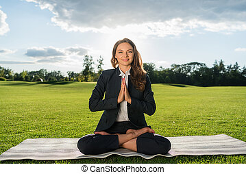 businesswoman meditating in park