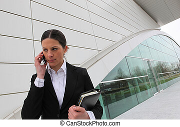 Businesswoman on a cellphone outside an office building