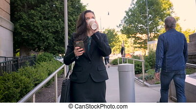 Businesswoman on mobile phone walking on walkway with to go coffee cup in 4k