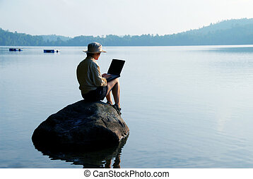 Businesswoman on rock - woman on a rock with a laptop in...