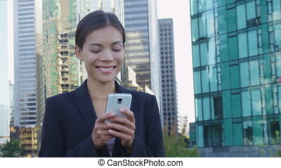 Businesswoman on smart phone sms texting using app in ...