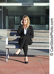 Businesswoman on the mobile phone sitting on a bench
