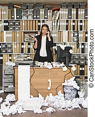 Businesswoman on the phone at the messy office