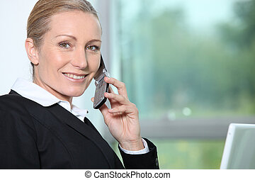 Businesswoman on the phone next to window.