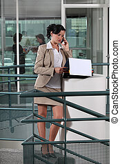 Businesswoman on the phone outside an office