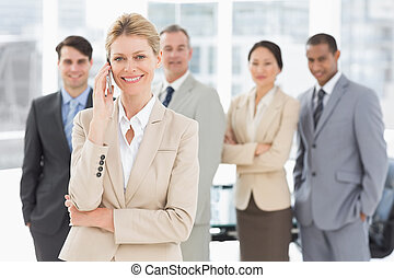 Businesswoman on the phone smiling at camera with team behind her in the office