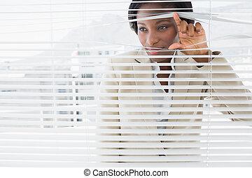 Businesswoman peeking through blinds