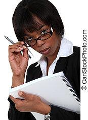 Businesswoman peering over her glasses