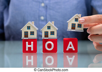 Businesswoman Placing House Models On HOA Cubic Blocks