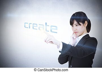 Businesswoman pointing to word create against white wall