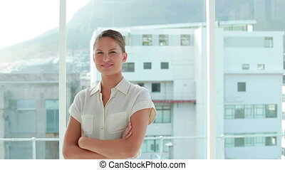 Businesswoman posing the arms crossed in front of a window...