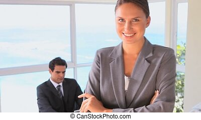 Businesswoman posing while her colleague is at his desk