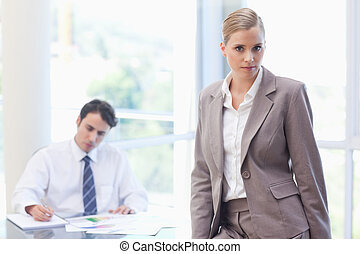 Businesswoman posing while her colleague is working
