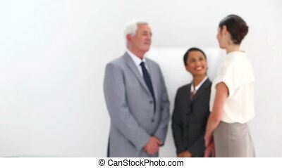 Businesswoman posing with colleagues talking