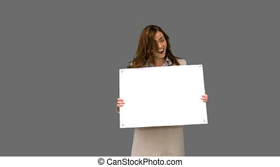 Businesswoman presenting blank board on grey screen in slow...