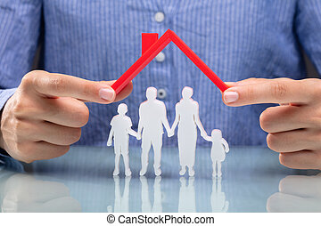 Businesswoman Protecting Family Figures With Red Roof