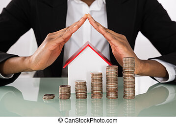 Businesswoman Protecting House Model With Stack Of Coins