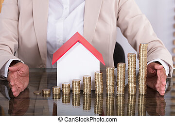 Businesswoman Protecting Stacked Coins And Model House