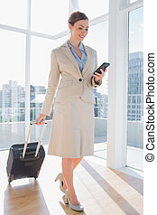 Businesswoman pulling her suitcase and checking her phone