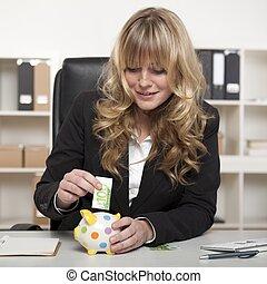 Businesswoman putting euro money in a piggy bank