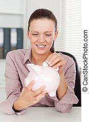 Businesswoman putting money in piggy bank