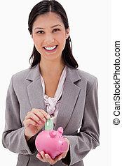 Businesswoman putting money into piggy bank