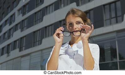Businesswoman Putting on Glasses