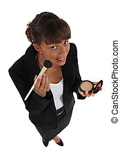 Businesswoman putting on makeup