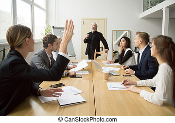 Businesswoman raising hand asking senior coach questions at team