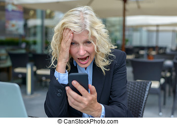 Businesswoman reacting in horror to her mobile phone running...